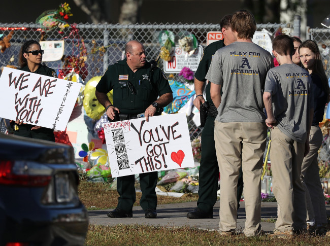 PARKLAND%2C+FL+-+FEBRUARY+28%3A++Broward+County+Sheriff+officers+welcome+students+as+they+arrive+at+Marjory+Stoneman+Douglas+High+School+as+students+arrive+to+attend+classes+for+the+first+time+since+the+shooting+that+killed+17+people+on+February+14++at+the+school+on+February+28%2C+2018+in+Parkland%2C+Florida.++Police+arrested+19-year-old+former+student+Nikolas+Cruz+for+the+17+murders.++%28Photo+by+Joe+Raedle%2FGetty+Images%29